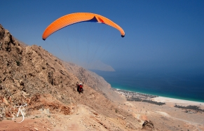 Arrive in style: paragliding into the Six Senses Zighy Bay. ©Travel+Style